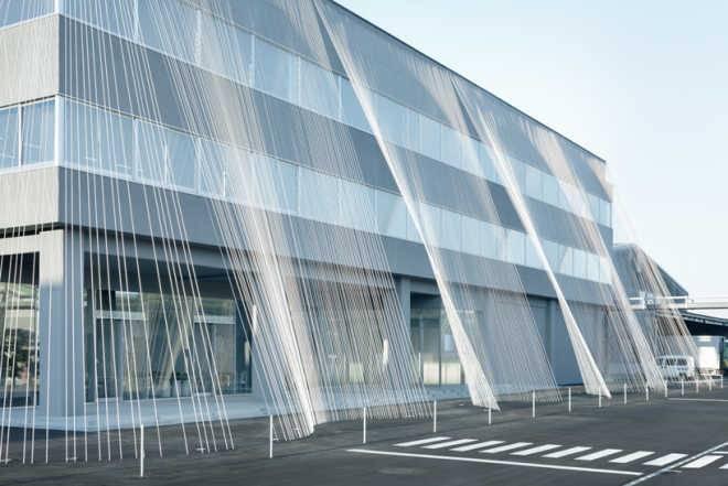 Здание с занавеской из углеродного полотна для предотвращения повреждений от землетрясений в Японии